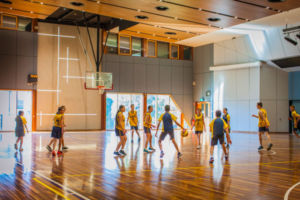 Students playing basketball in Clancy Catholic College school hall