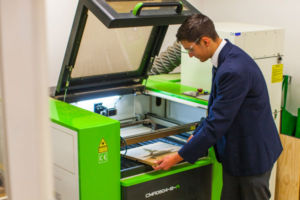 Student taking wood off laser cutter at Clancy Catholic College West Hoxton