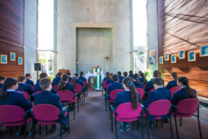 Parish priest leading students at Clancy Catholic College West Hoxton through prayer in school chapel