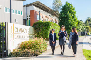 Mother walking with her daughters in front of Clancy Catholic College West Hoxton